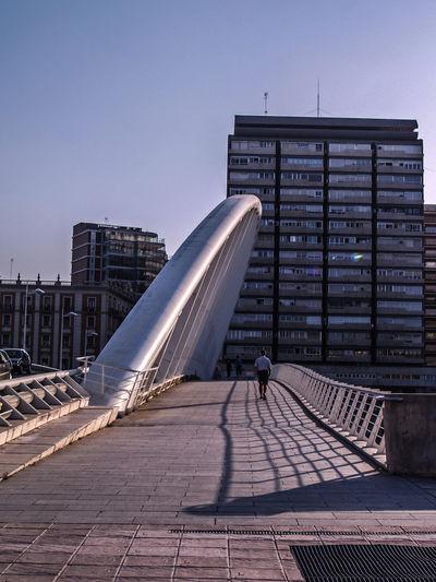 Rear view of man walking on bridge against buildings in city