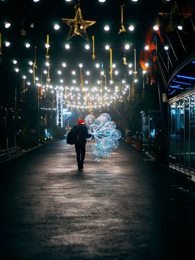 Rear view of person holding balloons while walking on illuminated street at night