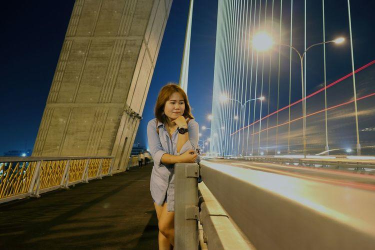 Smiling Woman Standing On Illuminated Bridge At Night