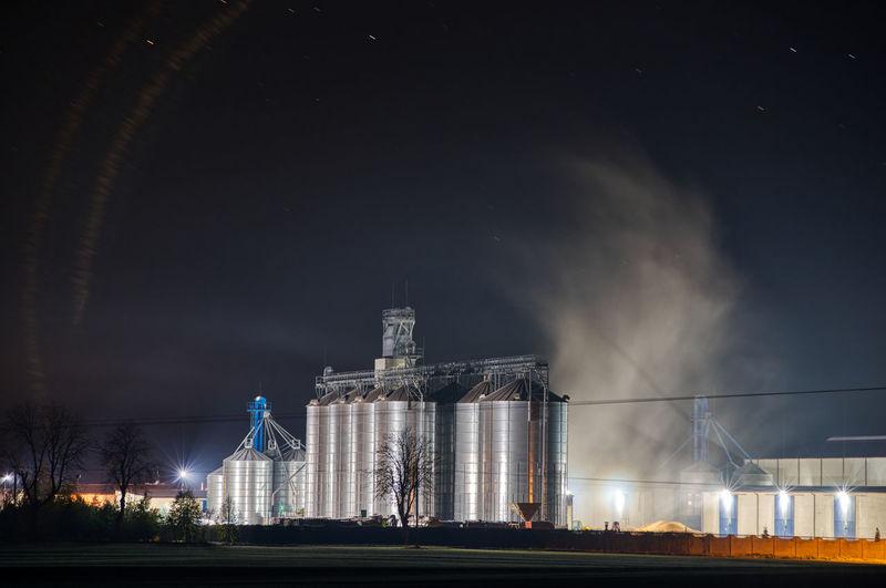 Grain dryer plant working at night with steam floating around it. modern farm. poland