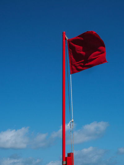 Low angle view of red flag against blue sky