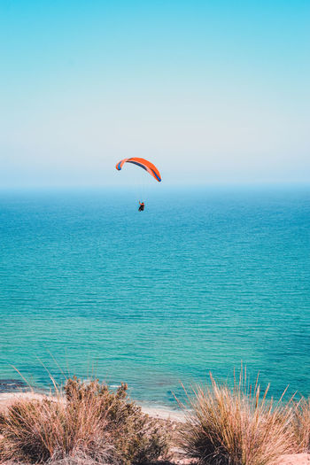 Scenic view of sea against sky with paraglider