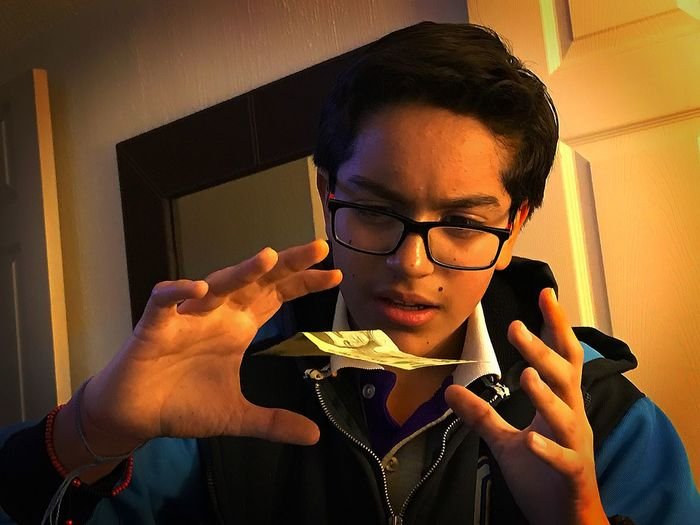 Close-Up Of Teenage Boy Levitating Paper Currency At Home