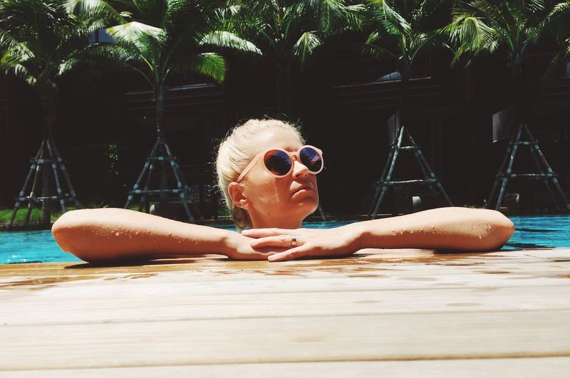 Young Woman Wearing Sunglasses In Swimming Pool
