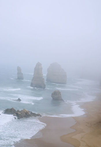 The so called 12 Apostel rocks at the Great Ocean Road in Australia on a misty morning 12 Apostles Australia Famous Great Ocean Road Misty Scenic Lookout Travel Beach Beauty In Nature Day Downunder Famous Place Fog Foggy Horizon Over Water Landmark Misty Morning Nature No People Ocean Outdoors Pacific Ocean Scenic View Scenics Sea Sky Tourism Tranquil Scene Tranquility Travel Destinations Water