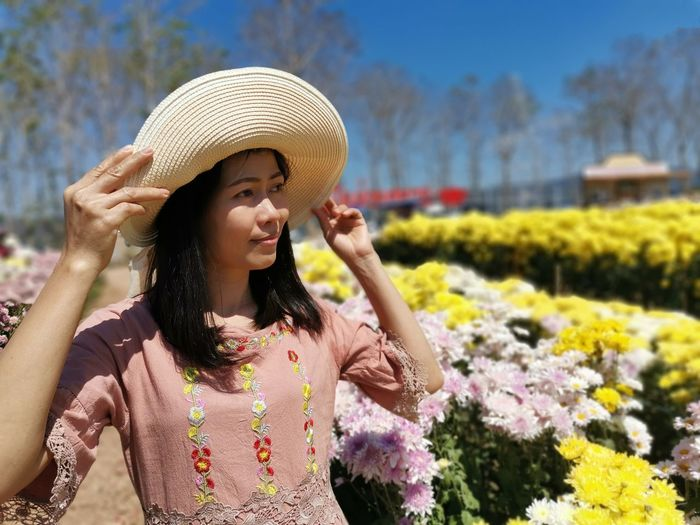Young woman with arms outstretched standing against plants