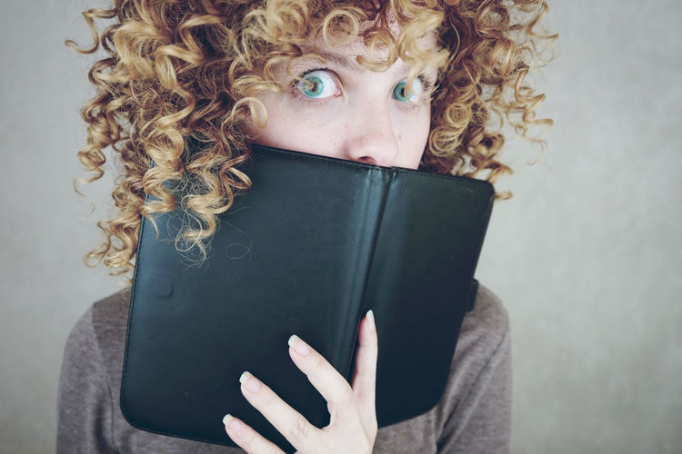 Portrait of shocked young woman covering mouth with book against gray background