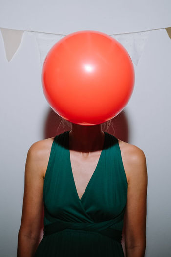 Midsection of a woman with red balloon against wall