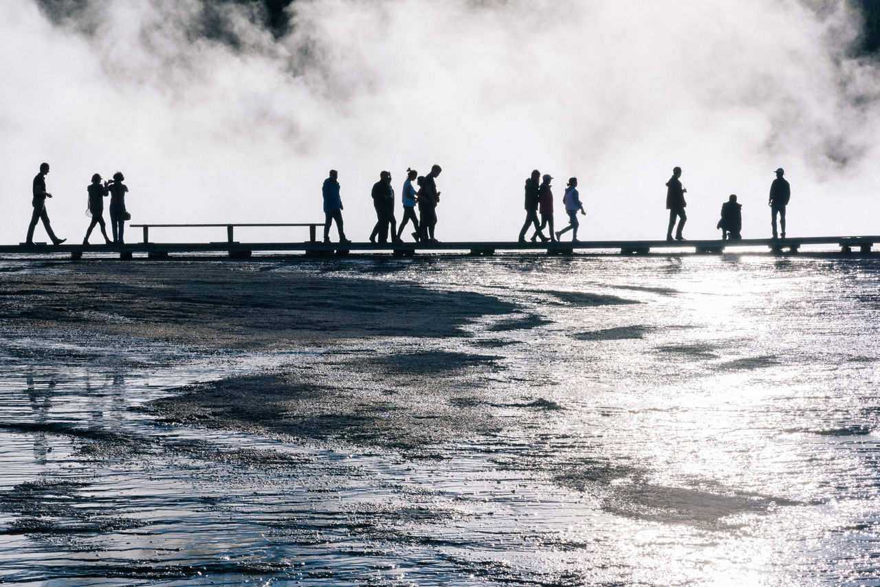 People Walking On Boardwalk By Field At Yellowstone National Park
