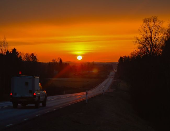 Pick-Up Truck On Country Road Against Orange Sky During Sunset