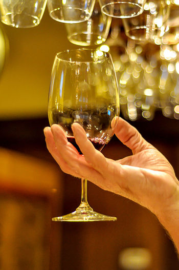 Hand holding wine glass against blurred background