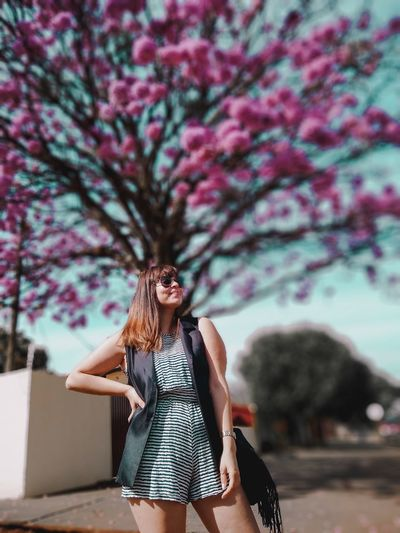 Young woman standing against flowering tree