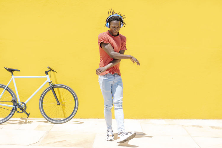Portrait of young man with bicycle standing against yellow wall