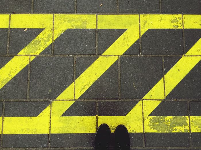 Low section of person standing on road by yellow markings