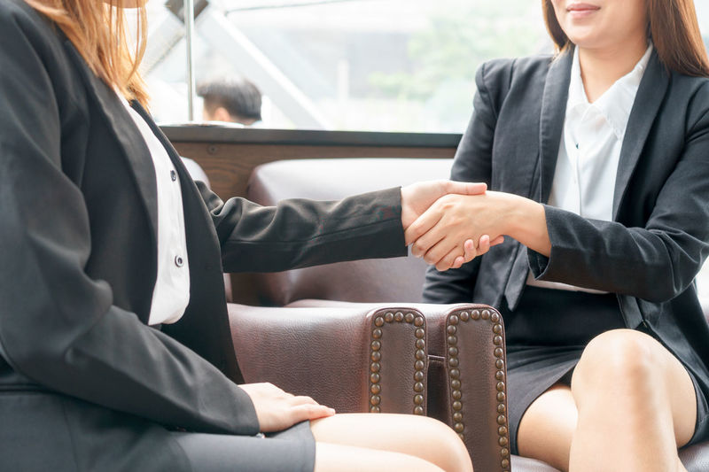 Businesswomen doing handshake while sitting on chairs in office