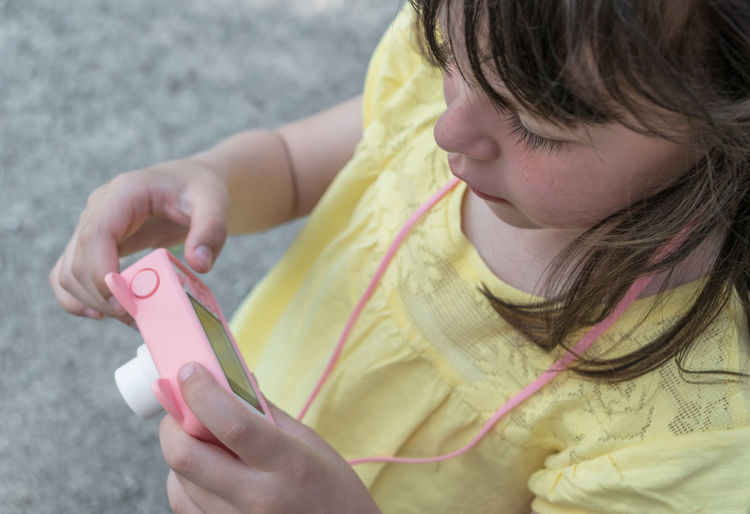 Cute little girl with a pink digital photo camera. Photography concept. Family vacation memories, taking photos using technology, leisure recreation lifestyle. Beautiful Beauty Camera Case Child Childhood Children Cute Digital Family Fun Girl Happy Holding Holiday Kid Leisure Lifestyle Little Nature Outdoors People person Photo Photograph Photographer Photography Picture Pink Portrait Pretty Soft Summer Sunny Taking  Technology Travel Use Vacation Young