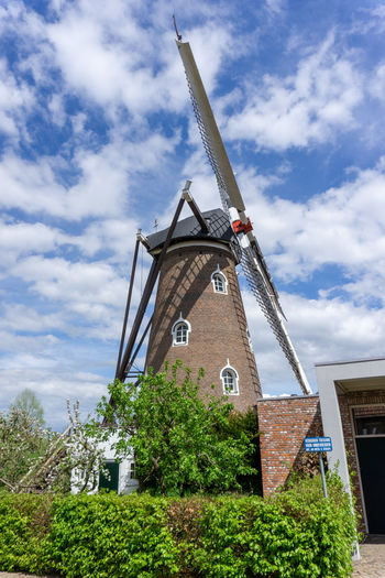 Low angle view of traditional windmill by building against sky