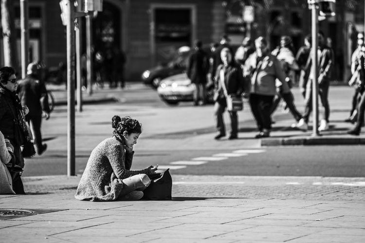 """Sitting on the street"" Barcelona Black & White Blackandwhite City City Life City Street One Person Outdoors Street Women Women Around The World The Street Photographer - 2017 EyeEm Awards My Best Photo"