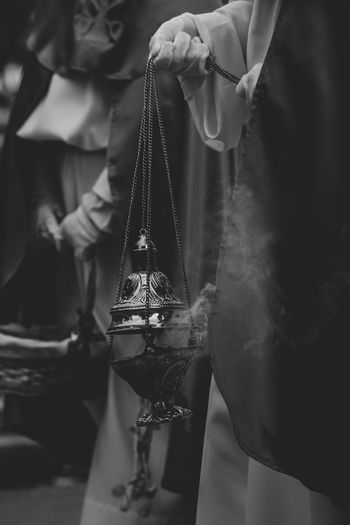 Midsection of person holding lanterns of frankincense in parade