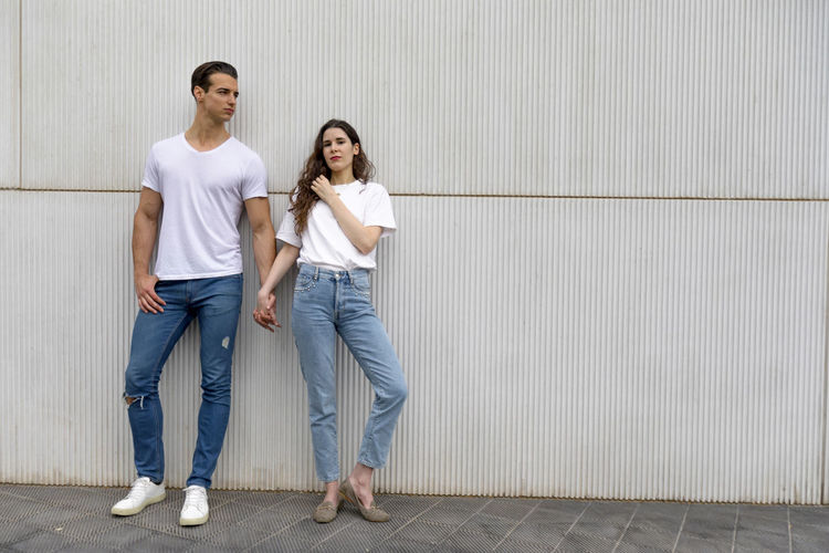 Couple Leaning Against Wall Holding Hands wearing casual clothes in a bright day Two People Casual Clothing Women Full Length Young Adult Young Women Standing Adult Wall - Building Feature Togetherness Men Architecture Front View Young Men Females Long Hair Couple - Relationship People Jeans Hairstyle Positive Emotion Concrete