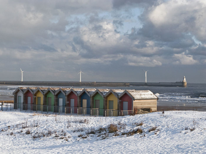 Colourful beach huts at Blyth in Northumberland contrast with winter snow Beach Huts Blyth Cloud Cloudy Cold Color Colorful Colour Europe European  Lighthouse Multi Colored Nature No People Northumberland Pier Scenics Sea Seasonal Seasons Sky Snow Uk Wind Turbines Winter