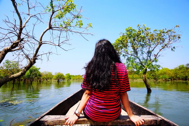 Rear View Of Woman Sailing On Rowboat In River Against Clear Sky