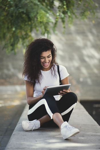 beautiful young woman sitting in the street while using happy her tablet Beautiful Woman Casual Clothing Connection Day Focus On Foreground Front View Full Length Hair Hairstyle Leisure Activity Lifestyles Looking Looking Down One Person Outdoors Real People Sitting Technology Wireless Technology Young Adult Young Women