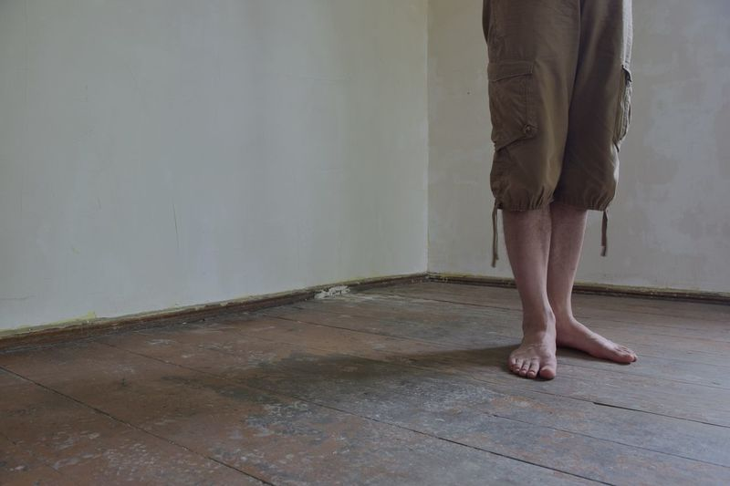 Low Section Of Man Standing On Hardwood Floor At Home
