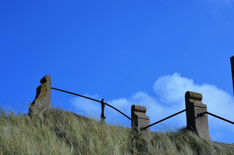 Low angle view of fence on field against blue sky