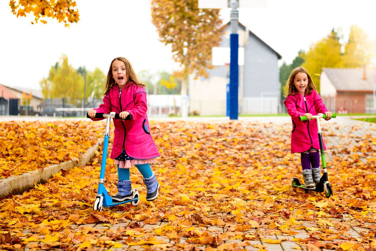 Girls Riding Push Scooters At Park During Autumn