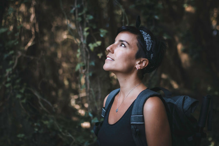 Portrait of young woman looking away in forest