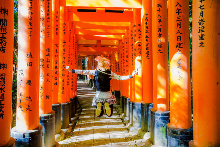 Kyoto, Japan - April 28, 2017: tourist woman walking under red torii gates of famous landmark Fushimi Inari shrine. Travel asia concept. Kyoto's popular landmark. Kyoto, Japan - April 28, 2017: Fushimi Inari Taisha is the most important Shinto shrine famous for its thousands of red torii gates.The lettering engraved on pole are the name of donated organizations Fushimi Fushimi Inari Taisha Fushimi Inari Taisha Shrine Gates Japan Photography Kyoto, Japan Shinto Shrine Shinto Temple TORII Torii Gate Tourist Tourist Attraction  Woman Fushimi Inari Kyoto Fushimi Inari Shrine Japan Culture Kyoto Kyoto Japan Kyoto,japan Kyotojapan Shinto Of Japan Shintoism Torii Gate Japan