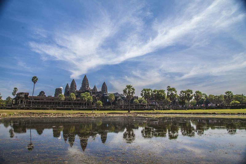 Pond near ankor wat temple against blue sky