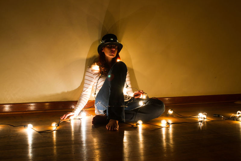 Young woman sitting on floor against illuminated wall