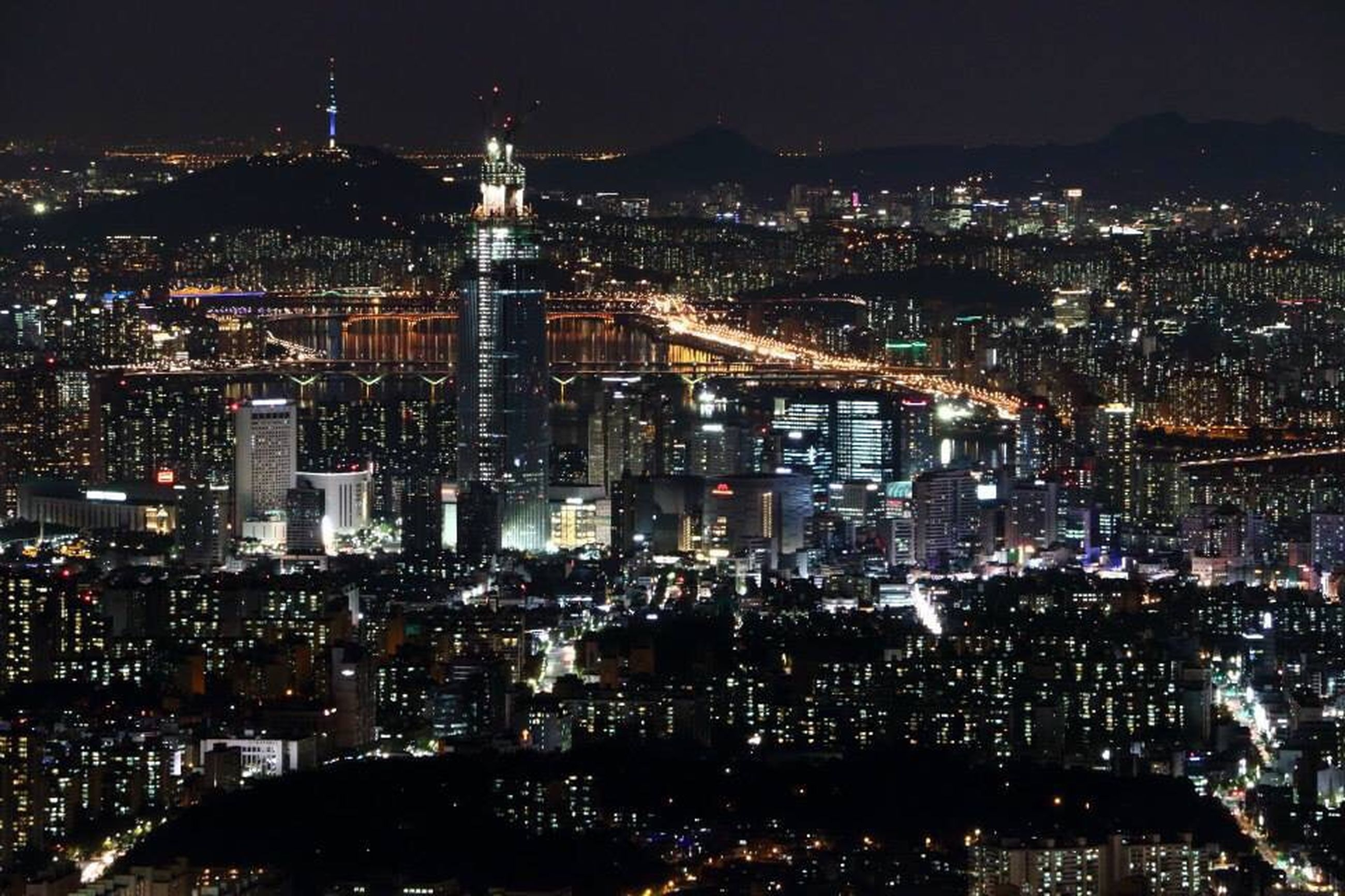 cityscape, night, illuminated, city, architecture, crowded, building exterior, built structure, skyscraper, high angle view, modern, aerial view, residential district, city life, capital cities, tower, tall - high, sky, travel destinations, office building