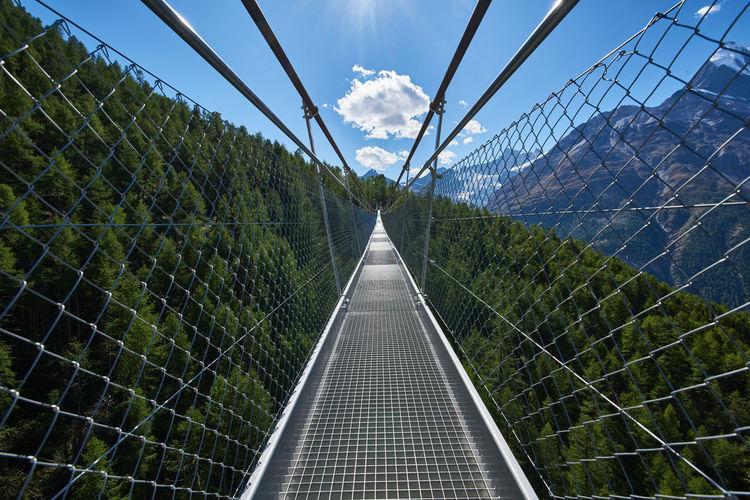 Railroad tracks on footbridge against sky