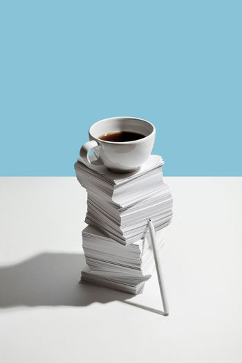 Stack of coffee on table against blue background
