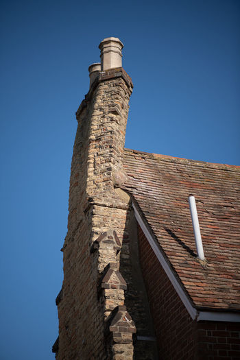 Low angle view of old building against blue sky