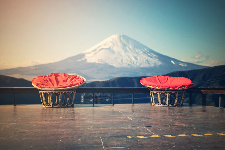 Red chairs and tables on table against mountain