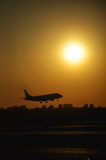 Airplane landing in the sunset Sky Air Vehicle Sunset Transportation Airplane Sun Mode Of Transportation Silhouette Sunlight No People Travel Airport Orange Color Flying Airport Runway