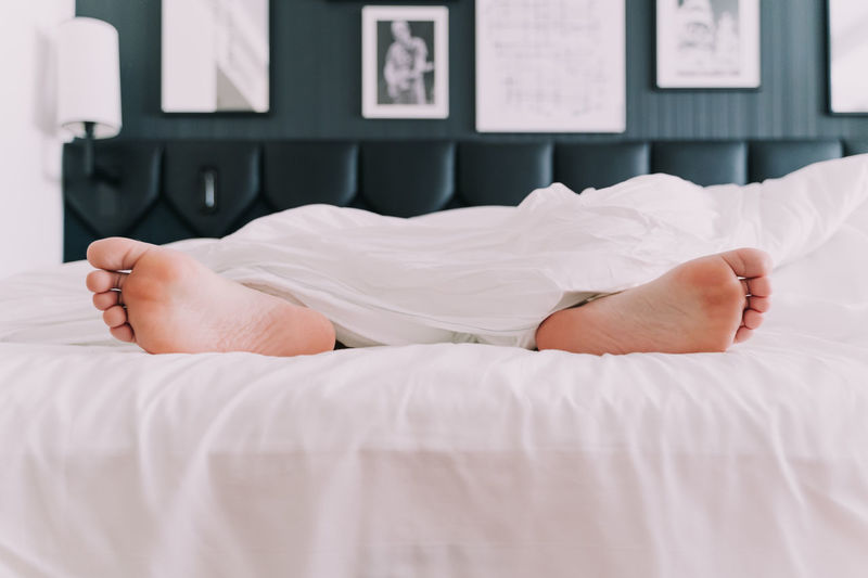 Low section of man relaxing on bed