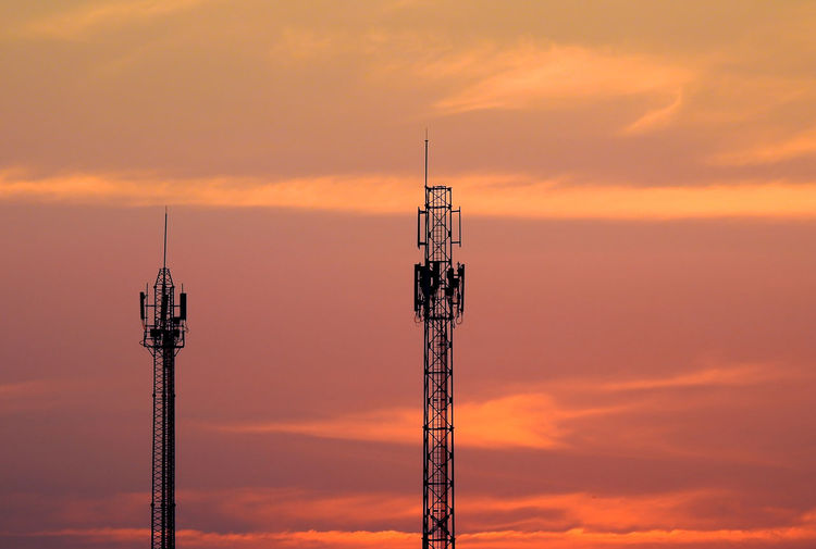 Low angle view of repeater towers against orange sky
