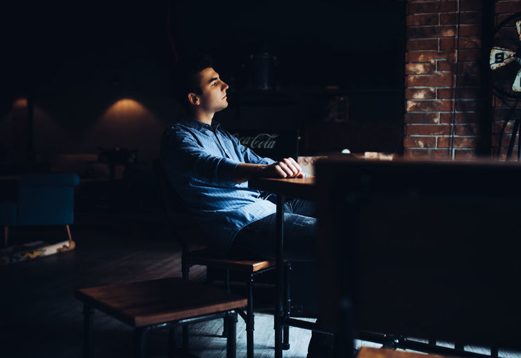 Man looking away while sitting on seat in cafe