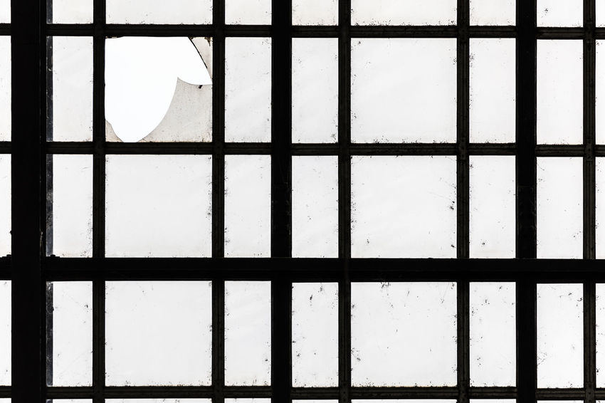 Metal construction with broken glass Bad Condition Aging Process Architecture Backgrounds Broken Built Structure Close-up Damaged Day Design Deterioration Full Frame Geometric Shape Glass - Material Indoors  Metal Monochrome No People Old Pattern Shape Square Shape Sunlight Transparent Window