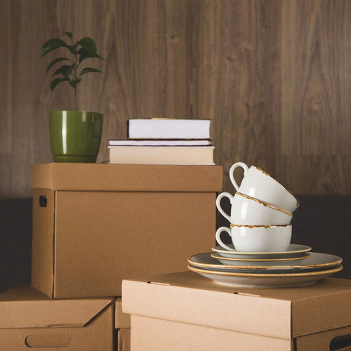 Crockery over blank boxes on sofa