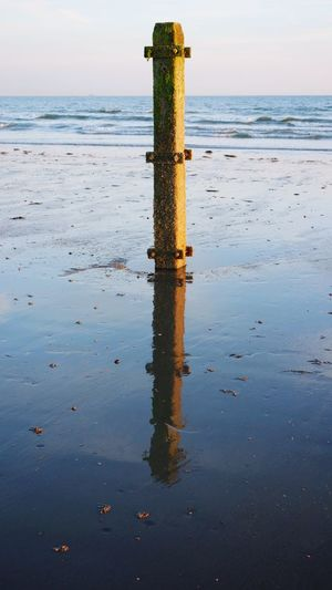 A wooden post reflecting in the wet sand on the beach. Nature_collection EyeEm Best Shots Selective Focus Close-up Silhouette Sunlight Wet Sand Copy Space Clear Sky Tidesout Waves EyeEm Selects Water Sea Sky Beauty In Nature Horizon Over Water Horizon Waterfront Nature Beach Reflection Tranquil Scene Scenics - Nature Wooden Post Land Day No People Outdoors Idyllic