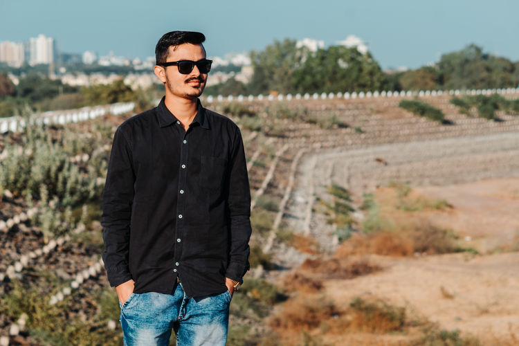 Young man wearing sunglasses standing on land