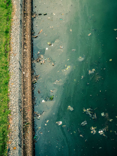 Top view of pinheiros river bank pollution and rocks.