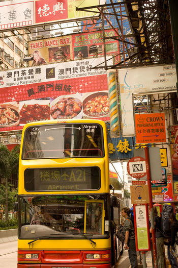 View of yellow bus on street in city