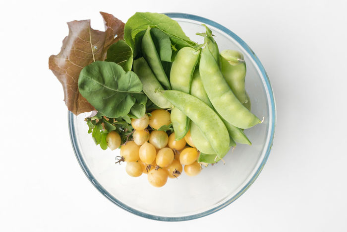 Freshly picked snow peas, lettuce and cherry tomatoes Bowl Close-up Cut Out Directly Above Food Food And Drink Freshness Green Color Green Pea Healthy Eating High Angle View Indoors  No People Raw Food Seed Still Life Studio Shot Vegetable Wellbeing White Background
